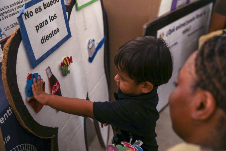 La Sargento de Segunda Clase del Ejército de los EE. UU. Chasidy Tenison, asignada al  buque hospital USNS Comfort, enseña fundamentos de nutrición a un niño en un puesto temporal de atención médica. (Foto: Especialista del Ejército de los EE. UU. Dedrick Johnson)
