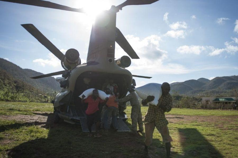 U.S. service members and citizens of Beaumont, Haiti, unload supplies from a U.S. Army CH-47 Chinook, Oct. 13, 2016. The service members are part of Joint Task Force Matthew, which has delivered more than 440 tons of supplies to Haitians affected by Hurricane Matthew. (U.S. Air Force Photo by Staff Sgt. Josh Kinney)
