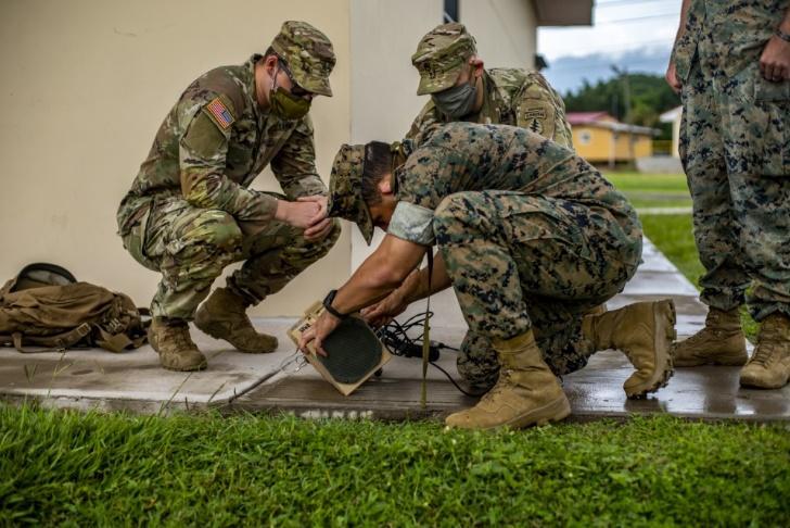 Infantes de marina de los EE. UU. asignados a la Fuerza de Tarea Marina Aeroterrestre de Propósito Especial del Comando Sur (SPMAGTF-SC en inglés), y soldados del Ejército de los EE. UU. pertenecientes a la Base de Operaciones Avanzadas, entrenan con un Altavoz Portátil de Última Generación  (NGLS-D en inglés), en la Base Aérea Soto Cano, Honduras, el 3 de septiembre de 2020. El NGLS-D puede emplearse en misiones de ayuda humanitaria, para enviar información importante a la población en un área extensa. Un grupo de aproximadamente 20 infantes de marina de la SPMAGTF-SC se sumó a la Fuerza de Tarea Conjunta Bravo, en la Base Aérea Soto Cano, para brindar apoyo a operaciones y ejercicios en la región de Latinoamérica y el Caribe. (Foto: Sargento del Cuerpo de Infantería de Marina de los EE. UU. Andy O. Martinez)