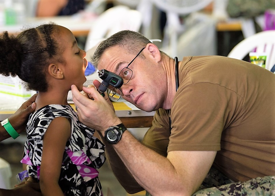 U.S. Navy Captain Michael Sullivan, a doctor assigned to the USNS Comfort, sees a Dominican girl for a general health check-up at a temporary medical treatment site in Santo Domingo, Dominican Republic. (Photo: U.S. Navy Mass Communication Specialist Third Class Danny Ray Nuñez Jr.)