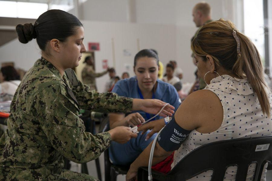 U.S. Navy Hospital Corpsman Marissa Monroe, from Bakersfield, California, assigned to the USNS Comfort, checks a patient's blood pressure. The Comfort's crew is working with health and government partners in Central America, South America, and the Caribbean to provide care on the ship and at land-based medical sites, helping to relieve pressure on national medical systems strained by an increase in Venezuelan migrants. (Photo: U.S. Army Specialist Jacob Gleich)