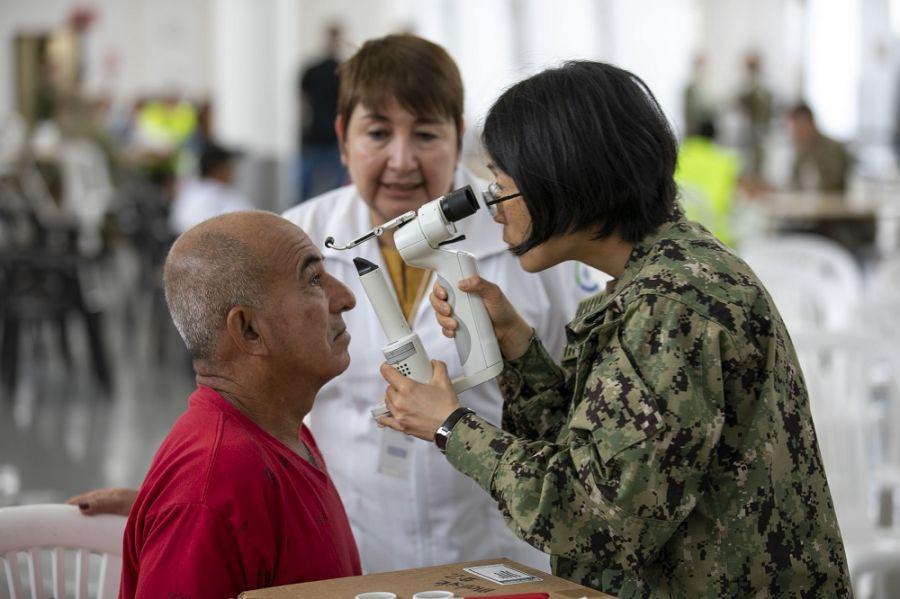 La Capitán de Corbeta de la Marina de los EE. UU.  Sandra Su, optometrista de Chicago, Illinois, realiza un examen de vista. (Foto: Especialista del Ejército de los EE. UU. Jacob Gleich)