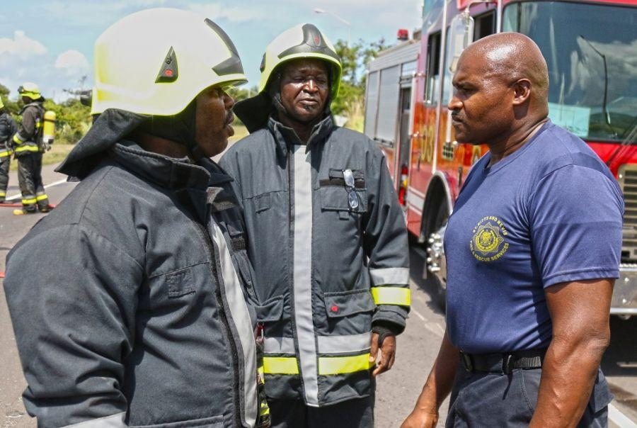 Lesroy Caines, (right) the station officer for Robert L. Bradshaw International Airport fire house, recieves a report from his firefighters while responding to the plane crash scenario during Tradewinds 2018 June 9, 2018, in Basseterre, St. Kitts. (U.S. Army National Guard photo by Staff Sgt. Shane Hamann, 102d Public Affairs Detachment)
