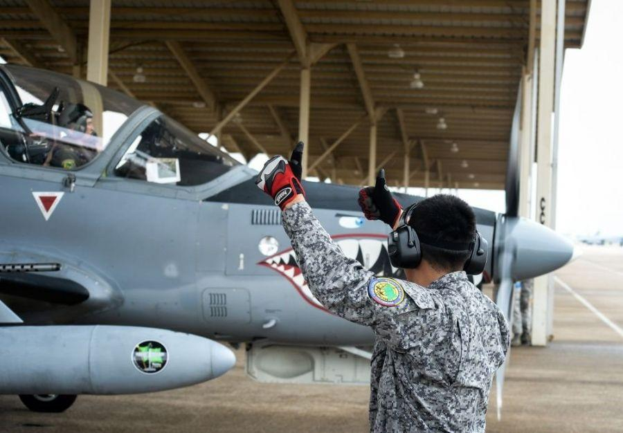 Colombian Air Force Technician 3rd Class Nestor Vanegas marshals an A-29B Super Tucano for take-off during exercise Green Flag East at Barksdale Air Force Base, La., on August 17th, 2016. Tech. Vanegas performed pre-flight checks on the aircraft and gave pilots the go-ahead signal for take-off. (U.S. Air Force photo / Senior Airman Mozer O. Da Cunha)