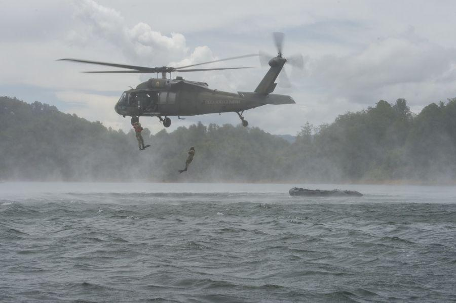 Colombian Air Force rescue troops jump from one of their UH-60 Black Hawk helicopters for a recovery exercise in water during Ángel de los Andes II, September 11, 2018. (Photo: U.S. Air Force Technical Sergeant Angela Ruiz)</br>Colombian Air Force-sponsored multinational exercise Ángel de los Andes II brought together more than 400 military, rescue, and medical personnel, as well as 21 aircraft, from the air forces of 12 nations to the highlands of Colombia, September 3-14, 2018. The exercise, in its second edition, seeks to strengthen interoperability among participants to save lives in humanitarian and natural disaster rescue missions and search and rescue in combat operations through mock situations.