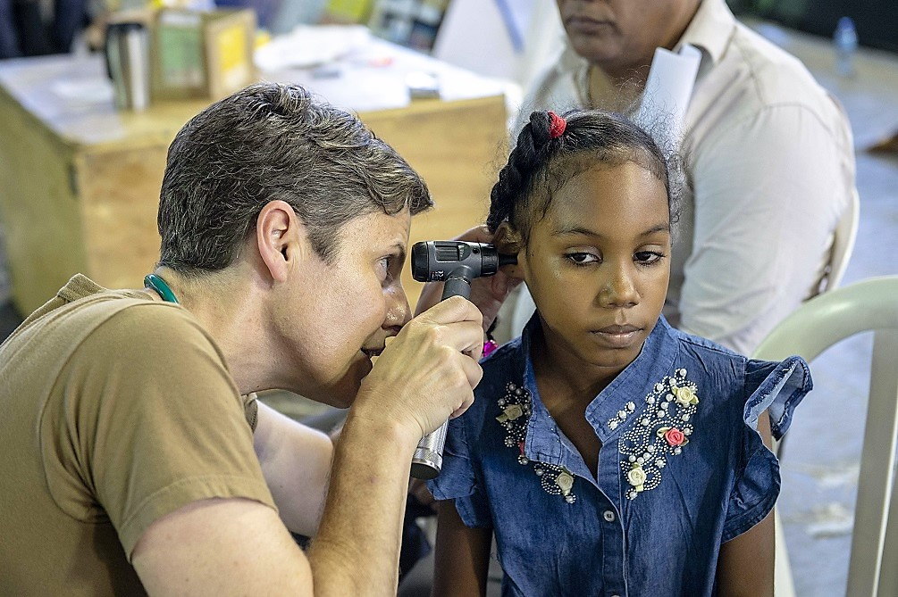 U.S. Navy Captain Jill Emerick, a doctor assigned to the USNS Comfort, examines a girl's ear at a temporary medical treatment site in Santo Domingo, Dominican Republic. (Photo: U.S. Navy Mass Communication Specialist Second Class Bobby J Siens)
