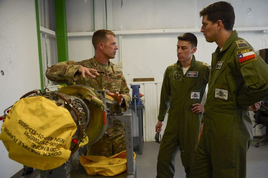 U.S. Air Force Master Sergeant Edward Bellus, 55th Helicopter Maintenance Unit, talks to Chilean Air Force Major Javier Del Rio and Lieutenant Erwin Caro, about helicopter engine maintenance during an H-60 Subject Matter Exchange at Davis-Monthan Air Force Base, Arizona, August 8, 2019. (Photo: U.S. Air Force Technician Sergeant Angela Ruiz)