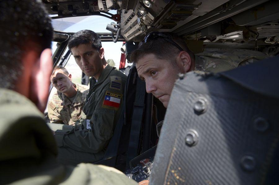 Pilotos da Força Aérea dos EUA e o Major da Força Aérea do Chile Javier Del Río ouvem o 1º Tenente da Força Aérea do Chile Erwin Caro, a bordo do HH-60G Pave Hawk, durante um intercâmbio entre especialistas em H-60, realizado na Base da Força Aérea de Davis-Monthan, no Arizona, no dia 8 de agosto de 2019. No início deste ano, quatro pilotos dos EUA viajaram a Santiago, Chile, para compartilhar informações sobre os helicópteros chilenos MH-60M Black Hawk. (Foto: Segundo-Sargento da Força Aérea dos EUA Angela Ruiz)