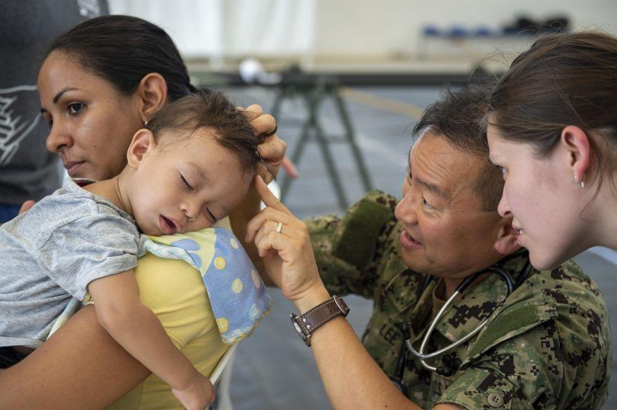 U.S. Navy Captain Gabriel Lee, a pediatrician assigned to Hospital Ship USNS Comfort examines a young boy with scabies at a temporary medical treatment site. (Photo: U.S. Navy Mass Communication Specialist Second Class Julio Martinez Martinez)