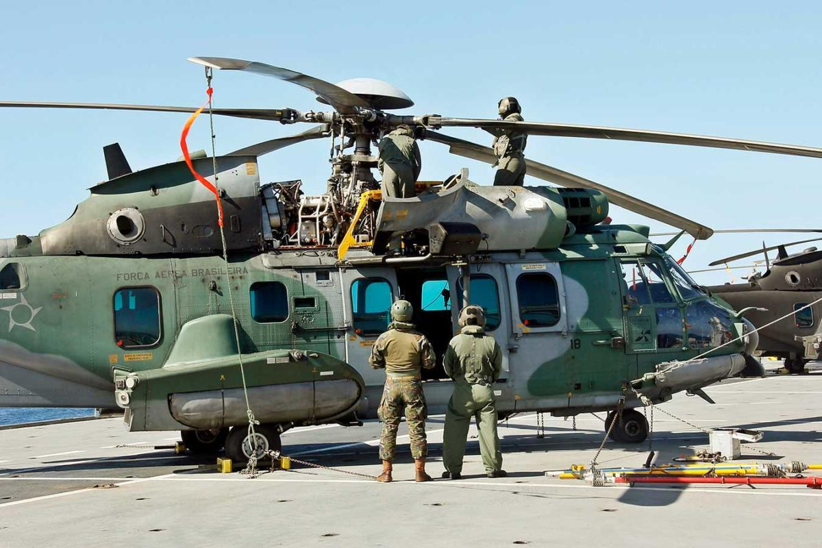 Members of the Brazilian Air Force fold the blades of an H-36 Caracal (H225M) aircraft during Operation Poseidon 2021, aboard the NAM Atlântico.