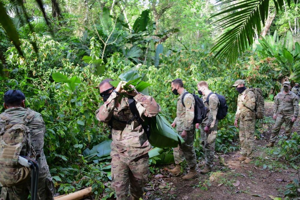 Membros da Força-Tarefa Conjunta Bravo (JTF-Bravo, em inglês) catam folhas para construir um abrigo, em um treinamento de sobrevivência durante o Exercício Mercúrio II, no Panamá, no dia 23 de janeiro de 2021. (Foto:  Terceiro-Sargento da Força Aérea dos EUA Elijaih Tiggs)