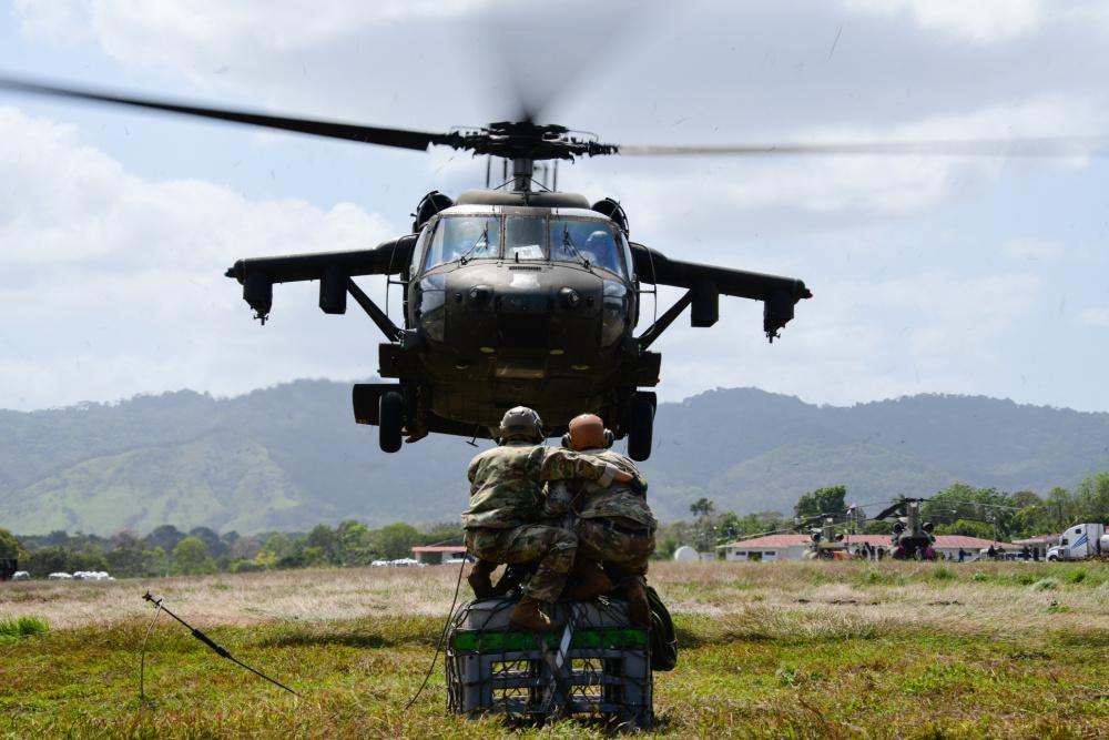 U.S. Army Colonel John Litchfield, JTF-Bravo commander, and another member of the same force prepare to attach sling load cargo onto a U.S. Army UH-60 Black Hawk helicopter assigned to JTF-Bravo's 1st Battalion, 228th Aviation Regiment, during Exercise Mercury II in Panama, January 25, 2021. (Photo: U.S. Air Force Staff Sergeant Elijaih Tiggs)