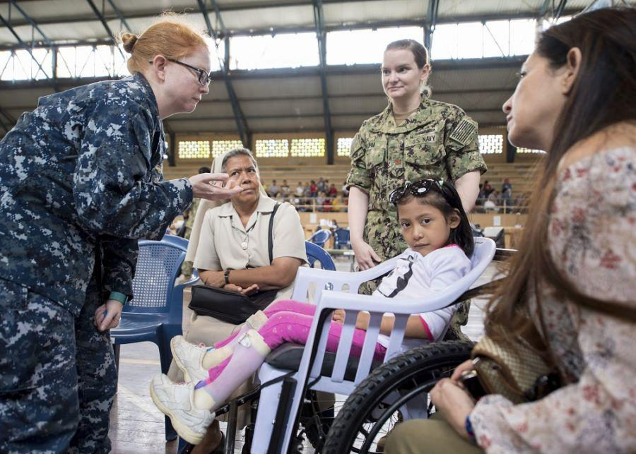 U.S. Navy Lieutenant Commander Kathleen Donahue and Lieutenant Commander Jessica Bluhm examine a young patient at the sports complex turned medical center for Continuing Promise 2018, in Puerto Barrios, Guatemala. (Photo: U.S. Navy Mass Communication Specialist First Class Mike DiMestico)