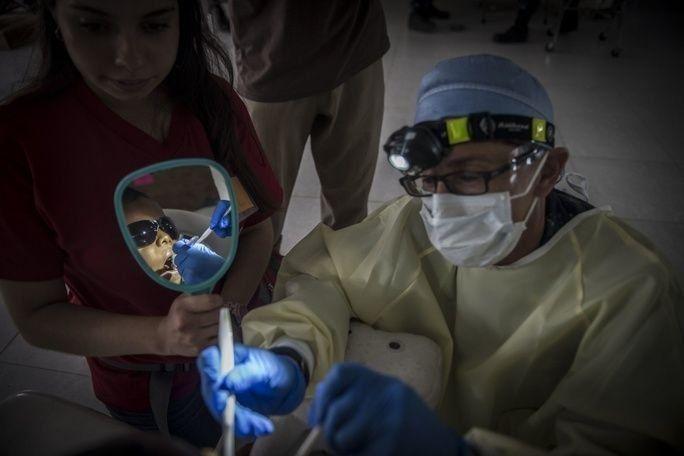 O CF Amy Bryer, dentista-chefe da Promessa Contínua 2017, demonstra como limpar corretamente os dentes, enquanto também trata um paciente colombiano na instalação médica da missão em Mayapo, na Colômbia. (Foto: Especialista de Comunicação de Massa de 2ª Classe Ridge Leoni/Câmera de Combate da Marinha dos EUA)