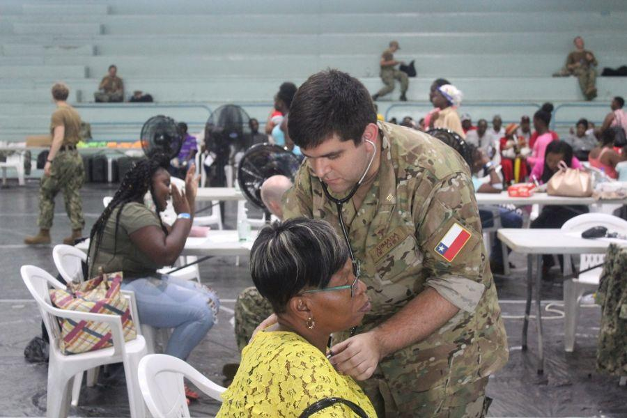 O Capitão-Tenente da Marinha do Chile Jorge Núñez, médico lotado no navio-hospital USNS Comfort, ausculta o coração de uma paciente em uma unidade médica provisória em Point Fortin, Trinidad e Tobago. (Foto: Steven Mcloud, Diálogo)