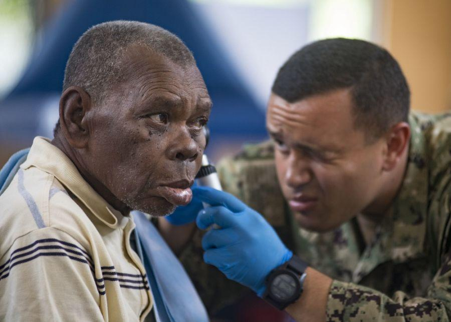 U.S. Navy Hospital Corpsman Brandon Romano screens a Guatemalan man's ear canal as part of a routine checkup at the sports complex turned medical center in Puerto Barrios, Guatemala, April 16, 2018. (Photo: U.S. Navy Mass Communication Specialist First Class Mike DiMestico)