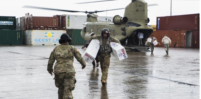 Infantes de marina de los EE. UU. con la Fuerza de Tarea Conjunta-Islas de Sotavento apilan cajas de lonas provenientes de la Agencia de los Estados Unidos para el Desarrollo Internacional mientras preparan abastecimientos para distribuirlos en el Aeropuerto Douglas-Charles en Melville Hall, Dominica.</br>La Fuerza de Tarea Conjunta-Islas de Sotavento (FTC-LI) brinda apoyo a las tareas de socorro en caso de desastre en Dominicana, tras el huracán María. La fuerza de tarea había brindado anteriormente asistencia a San Martín después del huracán Irma. Su misión es apoyar las operaciones de socorro de USAID a fin de salvar y mantener vidas, además de reducir el sufrimiento humano. Ante la solicitud de USAID, la FTC-LI ha desplegado a militares y aeronaves y de servicio para apoyar en la entrega de provisiones de emergencia a Dominica tras el huracán María. La fuerza de tarea es una unidad de las fuerzas militares de los EE. UU. integrada por infantes de marina, soldados, marinos y aerotécnicos, y representa la respuesta primaria del Comando Sur de EE. UU. ante los huracanes que han afectado al Caribe Oriental.