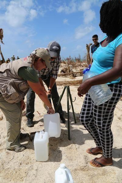 Anne Galegor, a representative of the U.S. Office of Foreign Disaster Assistance, helps a U.S. service member with Joint Task Force-Leeward Islands (JTF-LI) fill up water jugs for a local woman at a water distribution site in Saint Martin on Sept. 15, 2017. At the request of partner nations, JTF-LI deployed aircraft and service members to areas in the eastern Caribbean Sea affected by Hurricane Irma. (Photo: U.S. Army Captain Trisha Black)
