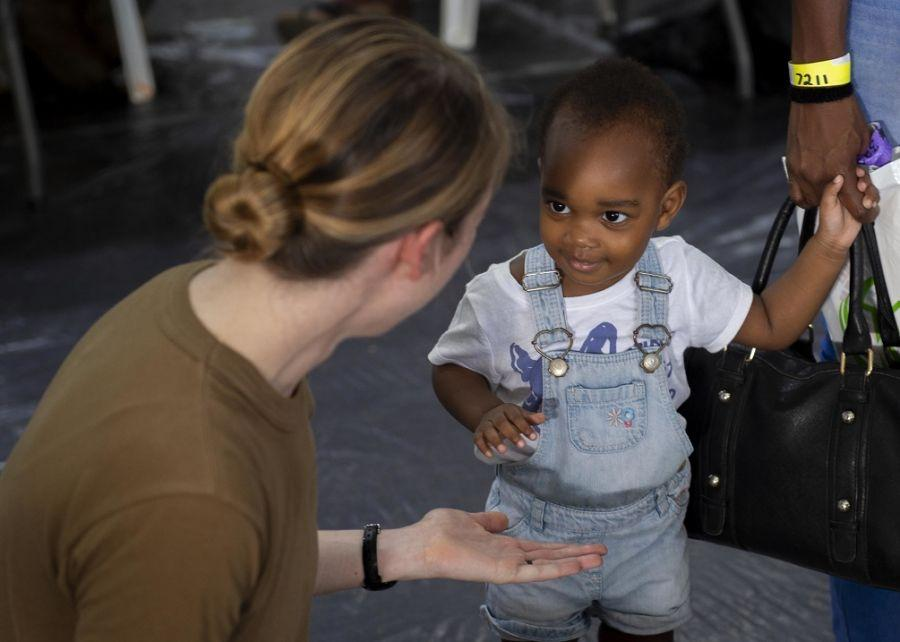USNS Comfort in Trinidad and TobagoU.S. Navy Lieutenant Sarah Fridley, a nurse assigned to U.S. Navy Hospital Ship USNS Comfort talks to a young girl while her and her family wait to receive care at a temporary medical treatment site in Point Fortin, Trinidad. (Photo: U.S. Navy Mass Communication Specialist Seaman Jordan R. Bair)