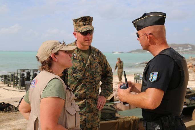 Anne Galegor, representante de la Oficina de Asistencia para Desastres en el Extranjero de los EE. UU. y el Coronel de la Infantería de Marina de los EE. UU. Michael V. Samarov, comandante de la Fuerza de Tarea Conjunta-Islas Sotavento, hablan con un miembro de la Gendarmería Nacional de San Martín, en un punto de distribución de agua instalado por militares estadounidenses, el 15 de septiembre. (Foto: Capitán del Ejército de los EE. UU. Trisha Black)