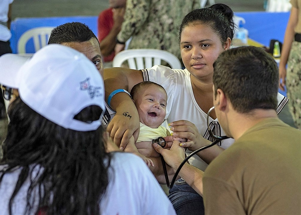 U.S. Navy Hospital Corpsman Third Class Nicholas Mauro examines a child at a temporary medical treatment site in Santo Domingo, Dominican Republic. (Photo: U.S. Navy Mass Communication Specialist Second Class Julio Martinez Martinez)