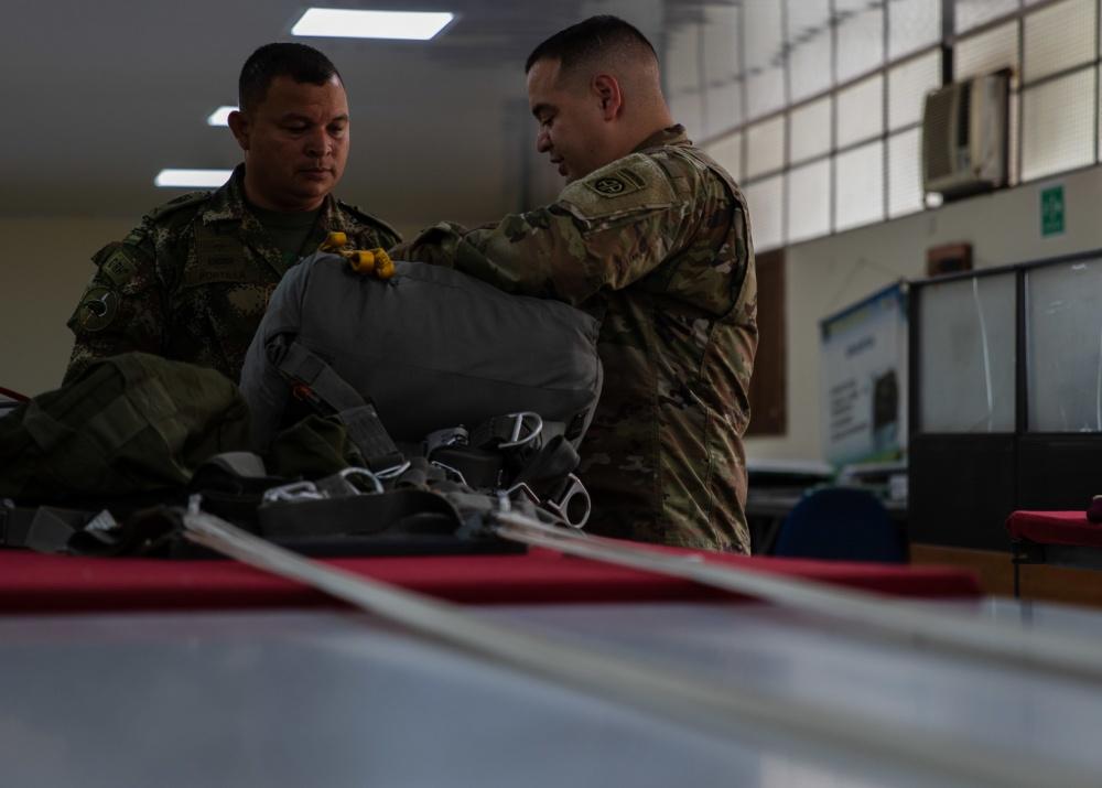 Preparadores de paraquedas do Exército da Colômbia e da 82ª Divisão Aerotransportada dos EUA discutem os procedimentos dos seus países, no dia 24 de janeiro de 2020. Os paraquedistas dos EUA e da Colômbia trabalham juntos durante o Exercício Força Dinâmica, em apoio ao Comando Sul dos EUA. (Foto: Subtenente do Exército dos EUA Alexander Burnett, da 82ª Divisão Aerotransportada)
